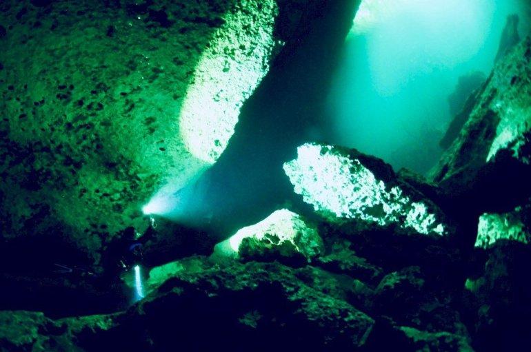 Une plongeuse fait une photo dans le cénote d'El Eden