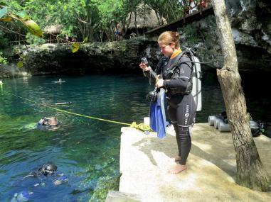 Une plongeuse s'apprête à se mettre à l'eau dans le cénote El Eden