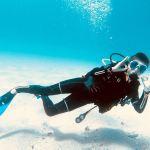 Un enfant qui fait le signe ok sous l'eau
