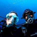 Un plongeur et une plongeuse se prennent en photo sous l'eau lors d'une plongée