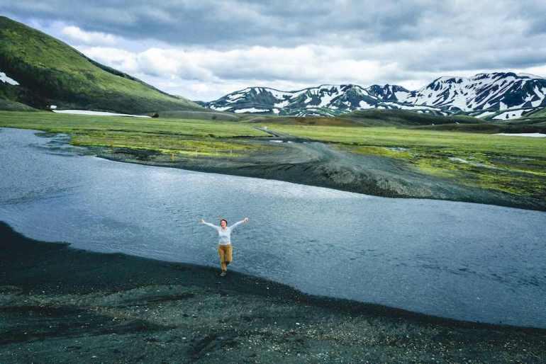 Une personne au bord de la rivière dans le Landmannalaugar en Islande