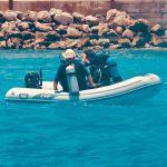 Deux personnes âgées sur un petit zodiaque s'apprêtent à se mettre à l'eau pour plonger