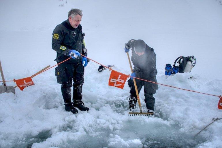 Deux plongeurs travaillent pour dégager la glace