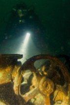 Un plongeur éclaire des machineries immergées