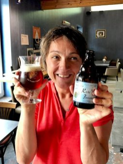 Hélène tient une bière de Rochefontaine en main