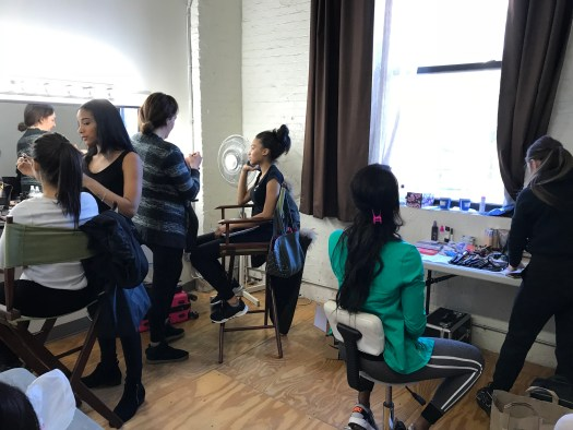 Hair and Makeup stations and artists working on their models.
