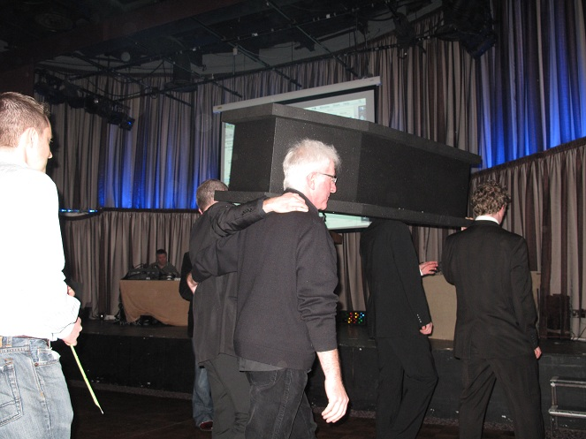 A Funeral procession down toward the stage. their holding white lillies and the coffin.