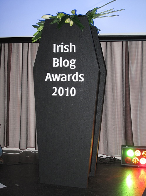The Irish Blog awards Coffin standing up right with lillies around it.