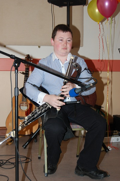 A picture of me playing the pipes on a small stage.