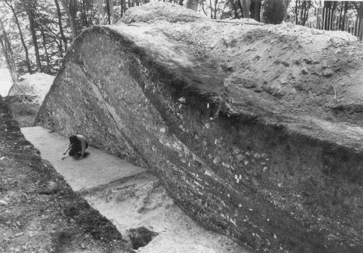 Image 01 - Section through the main rampart (1969). The figure crouches on the original ground surface. In the foreground is the quarry from which material for the first rampart was gathered. The stages in rampart building can be clearly seen.