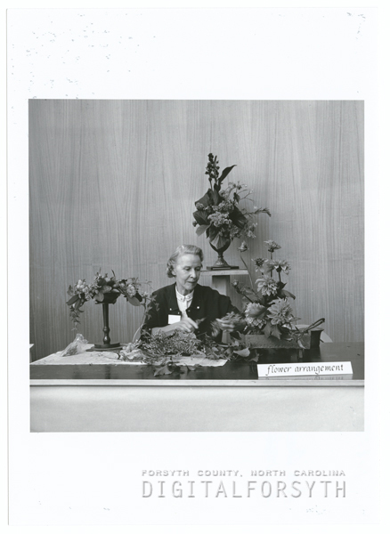 Woman arranging flowers at the Arts Council office at the James G. Hanes Community Center, 1964.