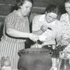 Tobacco farmers and families prepare a chicken stew at the tobacco curing barns, 1942.