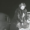 Woman demonstrating how to cover car lights to comply with the blackout regulations, 1942.