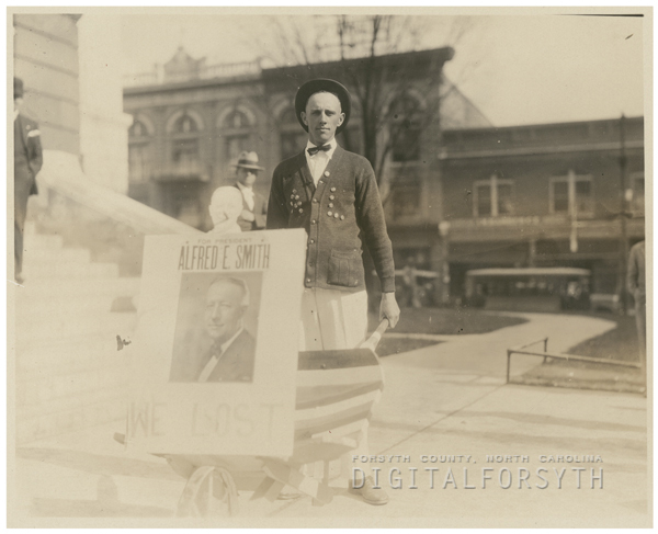 Man carrying a sign about the political campaign of Alfred E. Smith, 1928.