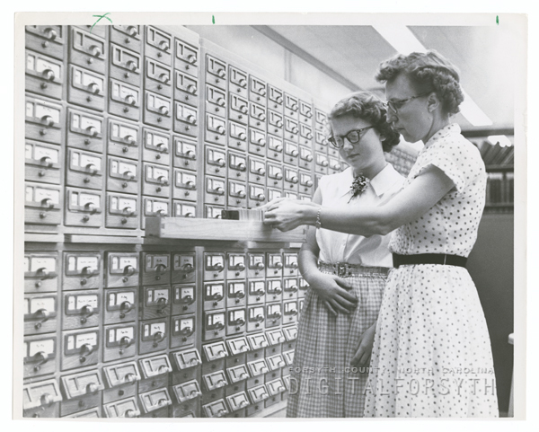 Librarian Mae Kreeger Tillman helping library patron use the card catalog.