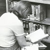 Library patron looking at books in the Humanities Department of the library, 1981.
