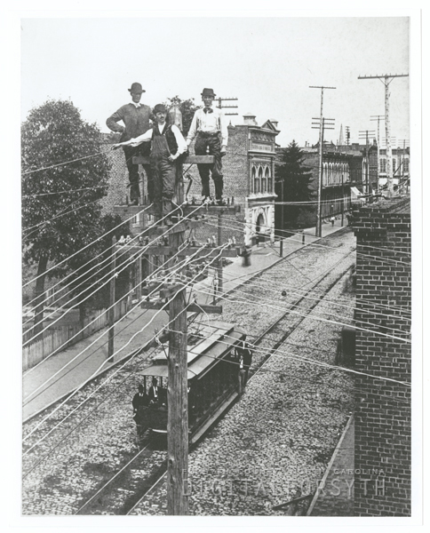 Men standing on a telephone pole over North Main Street.