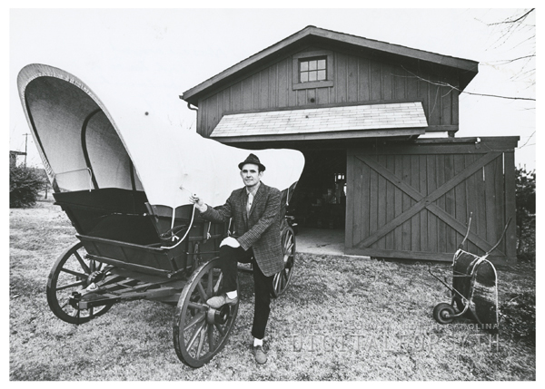 Glenn McGee with a covered Nissen wagon. The Loyd house is in the background, 1967.