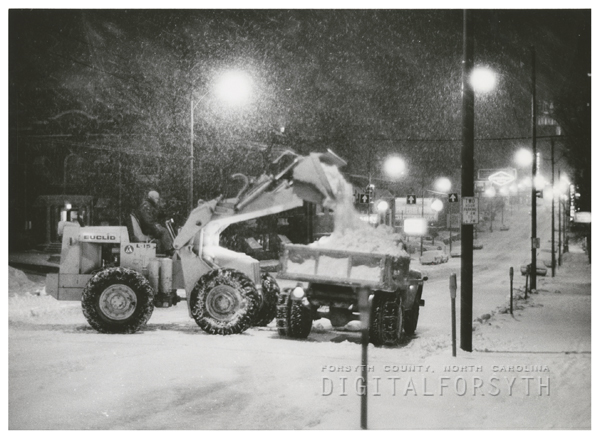 Snow being loaded into a dump truck on W. Fourth Street, 1966.