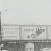 Man crossing a snowy West Fifth Street on crutches, 1962.