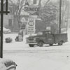 Man putting chains on his car in the snow at W. Fifth Street and Broad Street, 1962.