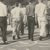 R. J. Reynolds High School students walking over the painted words on the street near the school, 1957.