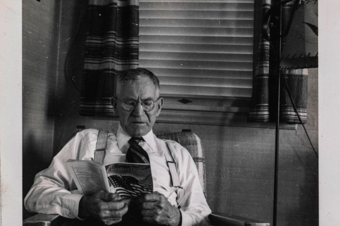 """Elderly man reads """"Readers Digest"""" in the living room - Undated"""