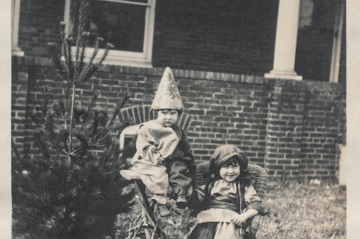 Two children in costumes sitting outside - Before