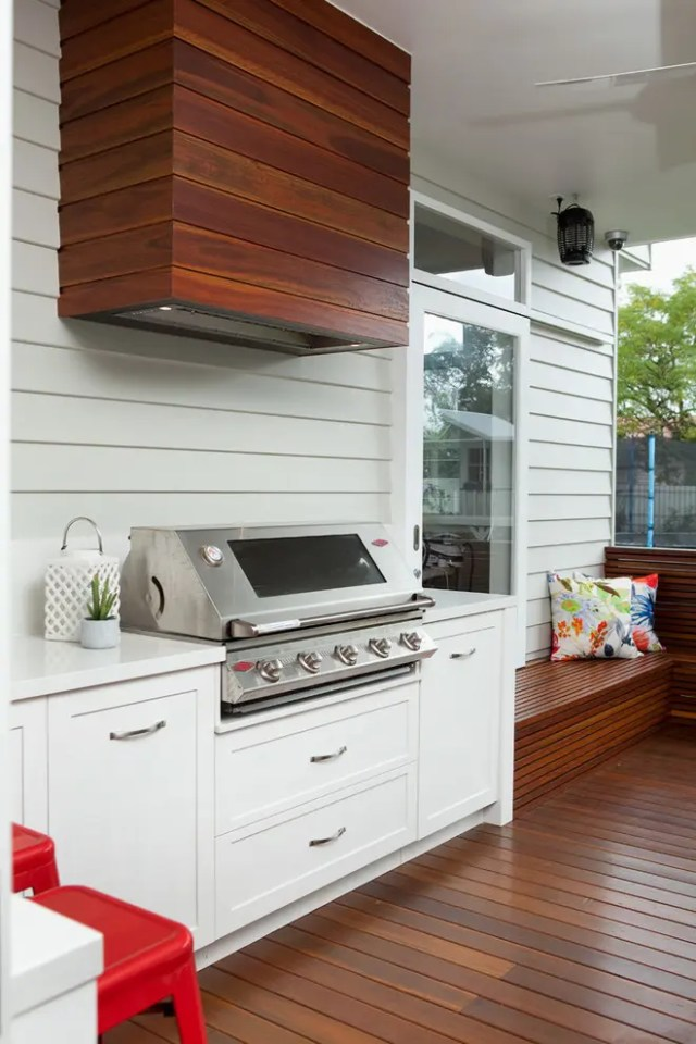 Covering a cooking hood with wood planks could help to blend it with a deck.
