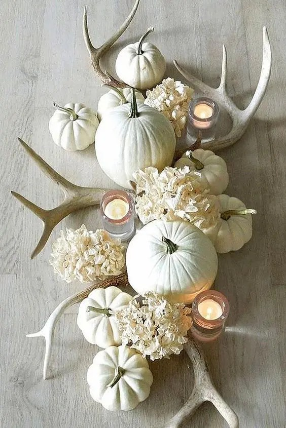 a white fall centerpiece of white hydrangeas, antlers, pumpkins and candles is chic and wow