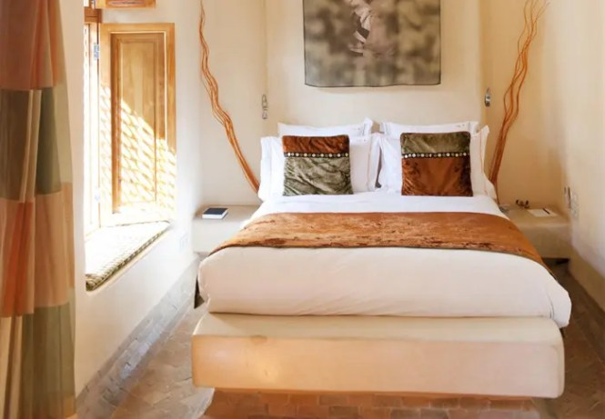 This Africa Inspired Bedroom Has Light Walls And Various Shades Of Ocher Used For Decor
