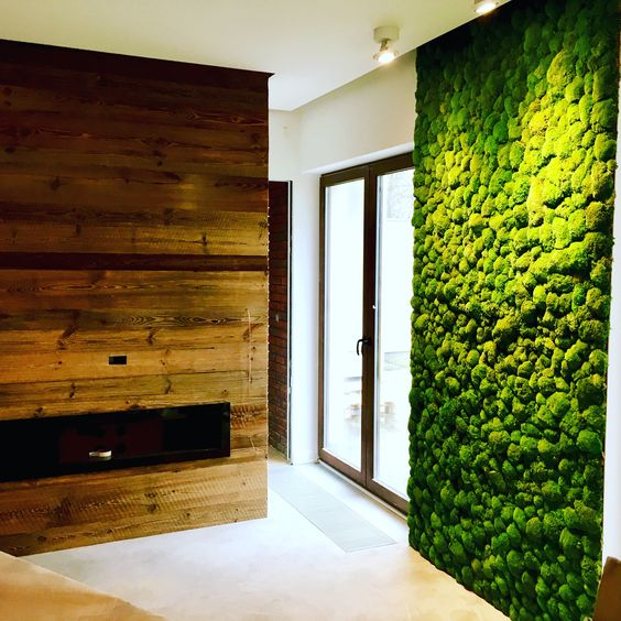 a fresh moss wall and a reclaimed fireplace wall bring a strong natural and relaxing fele to the space