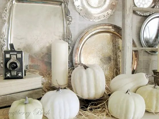 white hay, pillar candles, gourds and pumpkins make up a very exquisite and chic arrangement in the space