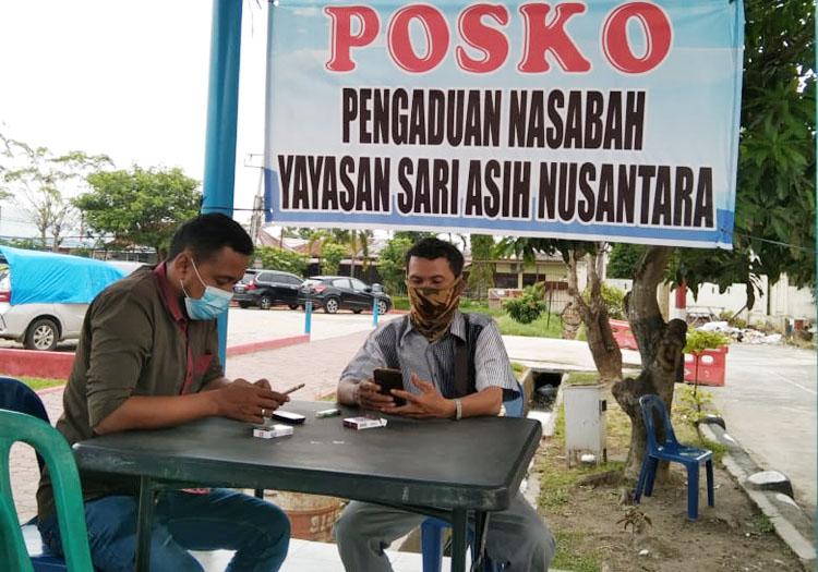 Dua pengunjung duduk di Posko Pengaduan Nasabah Yayasan Sari Asih Nusantara di depan gedung Satreskrim, Mapolresta Deliserdang.