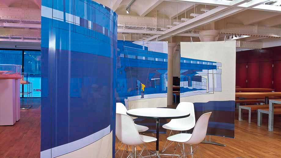 Curved fabric banner stands with modern art graphics being used as office partition screens