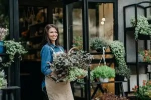 Small business owner with fresh flowers and sale in store. Florist work