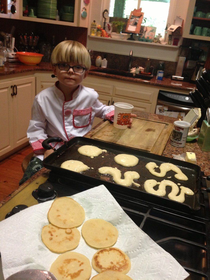 Adorable little chef in kitchen assisting with making pancakes