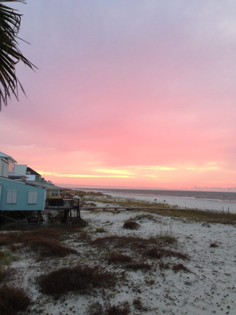 Beach view in Gulf Shores Alabama with colorful sunset