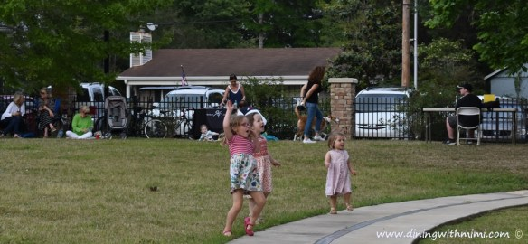 Trio of little girls and others enjoying the show at Hip Fairhope Outdoor Event www.diningwithmimi.com