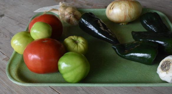 Tray loaded with fresh tomatoes, tomatillios, poblano peppers, onion and garlic for Smoky Roasted Poblano, Tomatillo and Tomato Salsa www.diningwithmimi.com