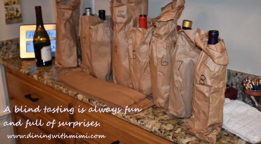 Bottles lined up for blind wine tasting theme Plan a wine tasting with friends www.diningwithmimi.com