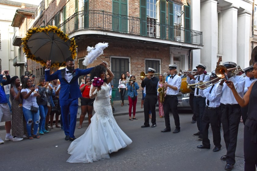 Beautiful Black Couple in full wedding attire dancing with parasols and Brass Band Need a quickie- Drop  into New Orleans for 48 hours www.diningwithmimi.com