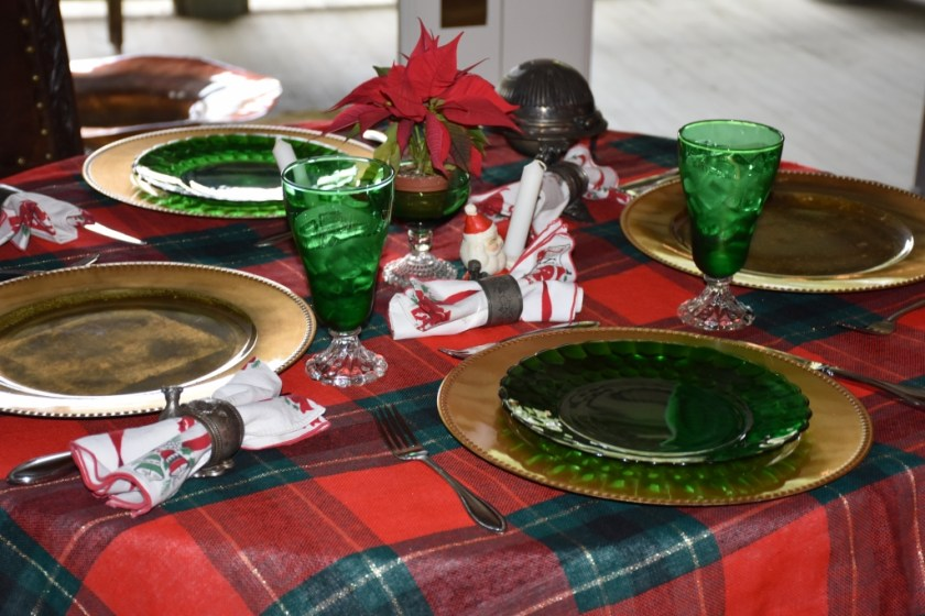 Round table with xmas table cloth  set with Fire King Forest Green glasses and bubble plates www.diningwithmimi.com