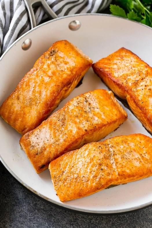 Seared salmon fillets in a frying pan.