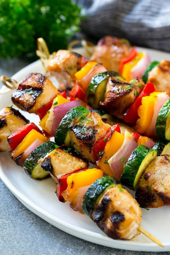A plate of grilled chicken kabobs made with marinated chicken and colorful vegetables.