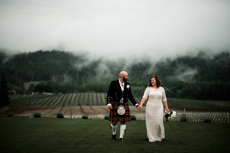 Bride and groom walking in the foggy vineyard after their wedding ceremony at Abbey Road Farm Wedding venue in Carlton Oregon.