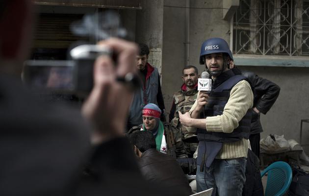 Abou Hussein en plein reportage, à Deir Ezzor le 19 février 2013 [Zac Baillie / AFP]