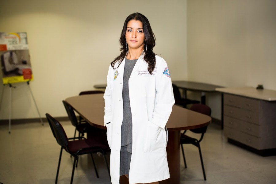 Radiologist Yania López Álvarez poses for a portrait at the Imaging Center of the University of Puerto Rico School of Medicine in San Juan, P.R., on April 11, 2018. The 35-year-old returned to her homeland last year to work with the island's population, leaving behind onerous job offers in the mainland. With a donation from Direct Relief, Lopez will be able to practice her specialty and create her most desired workshop doing Contrast-Enhanced Spectral Mammography at the center, as the new x-ray machine is expected to arrive later in the year. Currently, the young doctor spends most of her time working with radiology residents at the Medical Center of Puerto Rico, where the UPR School of Medicine is located at. Lopez, director of the Imaging Center, poses in the room where the new x-ray machine will be placed at. (Erika P. Rodriguez for Direct Relief)
