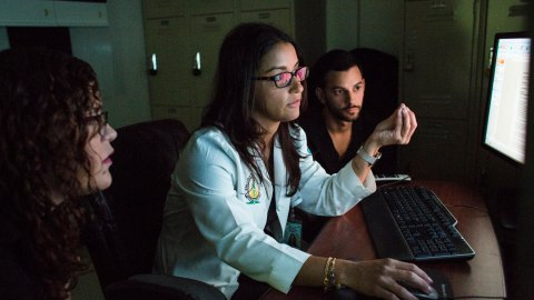 Radiologist Yania López Álvarez (center), discusses the patient cases of her residents, Amanda P. Marrero González and Manuel Betancourt Robles, at the Medical Center of Puerto Rico in San Juan, P.R., on May 10, 2018. Lopez, director of the Imaging Center of the University of Puerto Rico School of Medicine, returned to her homeland last year to work with the island's population, leaving behind onerous job offers in the mainland. With a donation from Direct Relief, the 35-year-old will be able to practice her specialty and create her most desired workshop doing Contrast-Enhanced Spectral Mammography at the center, as the new x-ray machine is expected to arrive later in the year. Currently, the young doctor spends most of her time working with radiology residents at the public hospital, where the UPR School of Medicine is located at. (Erika P. Rodriguez for Direct Relief)