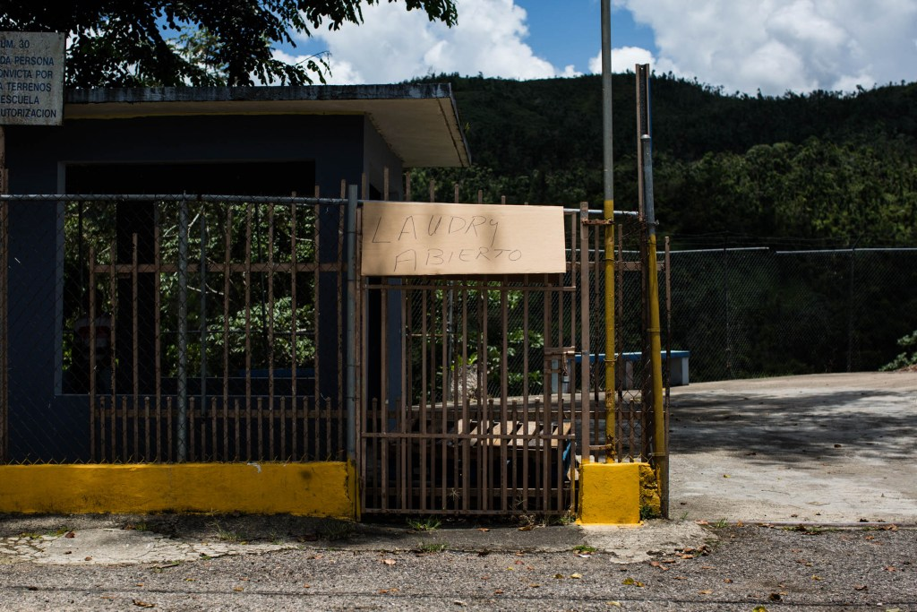 A sign announces to residents that the new solar-powered laundry room at the non-profit Acción Comunitaria del Viví, Inc., in Barrio Vivi Arriba, Utuado, Puerto Rico, is open for use on May 26, 2018. Inside the former public school, the group, funded by Direct Relief, opened a free laundry service for the two nearby communities who have been without power for over eight months. The group, coordinated by Miguel Morales, serves as a community and aid center in the aftermath of Hurricane Maria. Many of the residents of the mountainous area are elderly and underprivileged. (Photo by Erika P. Rodríguez for Direct Relief)
